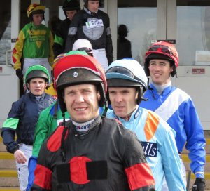 Richard Johnson - in the colours of The Knot Is Tied's owners - leads the jockeys out