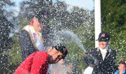 ERM has brought a little of Formula-one's pizzazz to eventing with podium interviews & bubbly: here Jonelle Price is on the right showing her expertise at spraying champagne! (Photo by ERM TV)