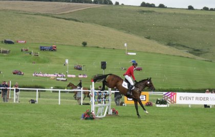 The main ring at the International Horse Trials with the cross country course beyond it - and sheep on the downs
