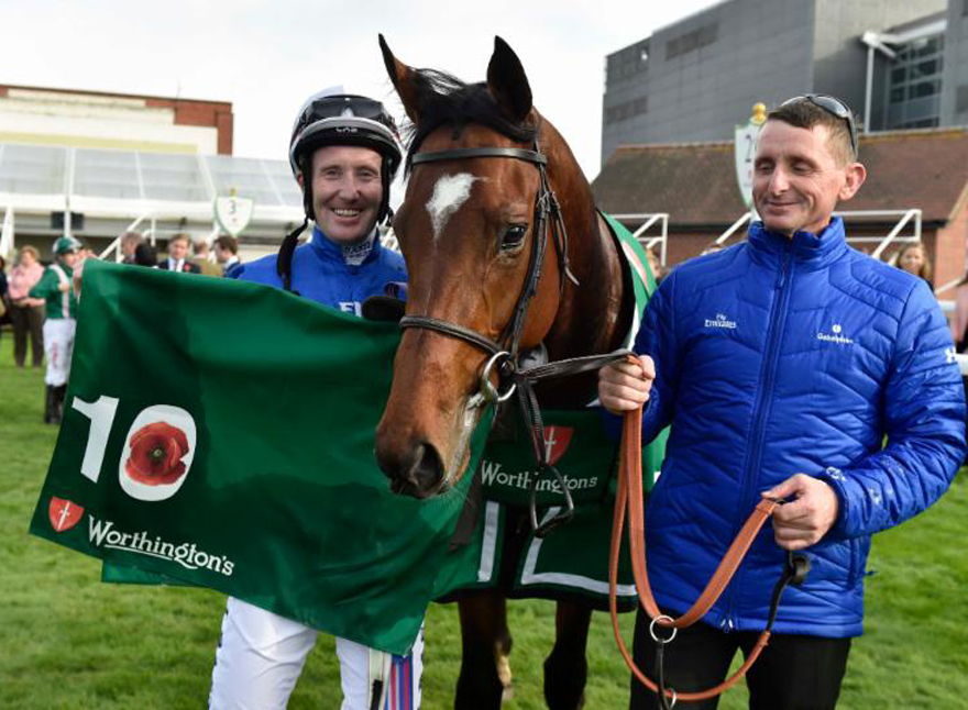 "Best Solution, winner of the G3 Worthington's ""Indigo Leisure"" Stakes, & jockey Pat Cosgrave with the special Poppy saddle cloth marking the 10th anniversary of Newbury's Armed Forces Raceday (Photo courtesy Newbury Racecourse)"